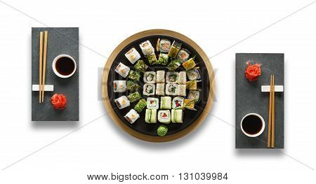 Japanese food restaurant, sushi maki gunkan roll plate or platter set. Set for two with chopsticks, ginger, soy sauce and wasabi. Sushi at black stone isolated at white background. Top view, Flat lay.