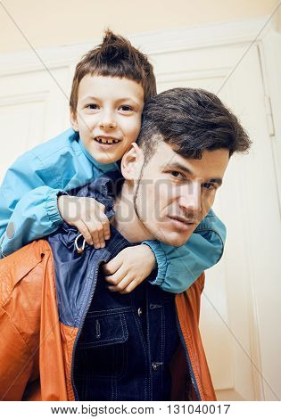 young handsome father with his son fooling around at home together, lifestyle people concept