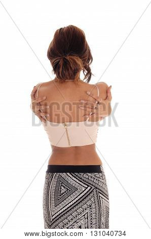 A young woman standing from the back with her arm's around her upper body hugging herself isolated for white background.