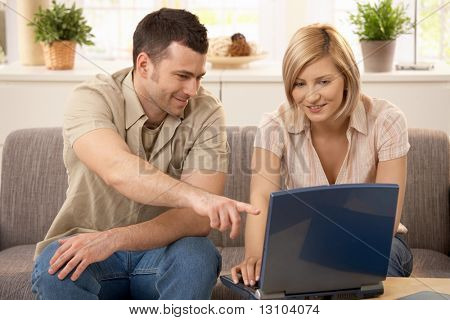 Young man pointing at laptop computer screen, pretty girlfriend smiling.