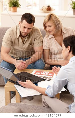 Young couple listening to estate agent showing new house on laptop.