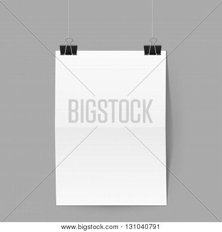 White paper folded in half hands on black clips on grey background