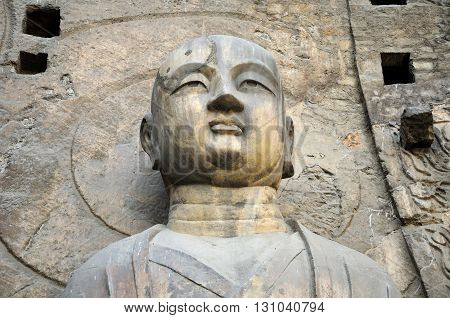 A stone Buddha statue Fengxiansi cave at Longmen grottoes in Luoyang China Henan province.
