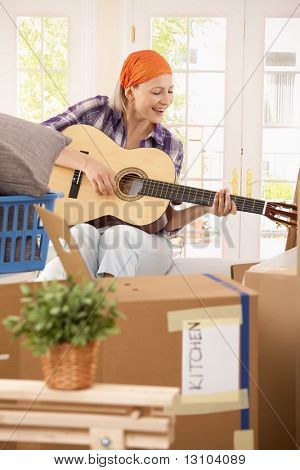 Smiling woman sitting in middle of boxes, playing guitar at break of moving house.