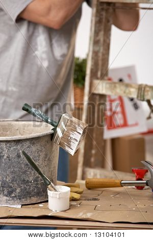 Focus on painting equipment, brush and bucket, man standing by ladder in background.