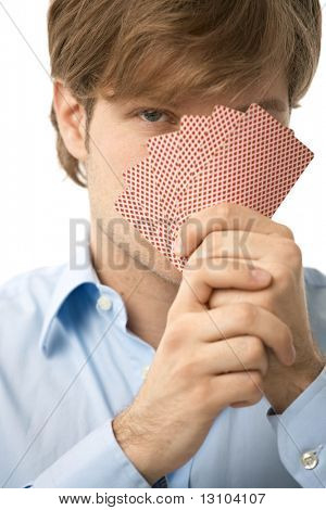 Young man looking over a hand of playing cards. Isolated on white.
