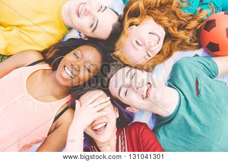 Group of four friends laughing out loud outdoor sharing good and positive mood.
