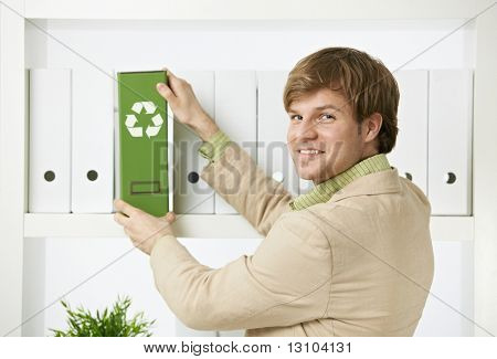 Businessman removing green folder with recycling symbol from shelf, looking back at camera, smiling.