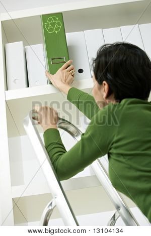 Office worker on ladder removing green folder with recycling symbol from shelf.