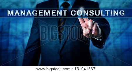 Businessman is touching MANAGEMENT CONSULTING on an interactive touch screen. Business metaphor and industry concept for the practice of professional assistance with organisational change.