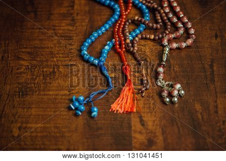 Various islamic prayer beads placed together on wooden background. Islamic religious background.