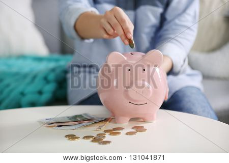 Female hand putting coin into piggy bank