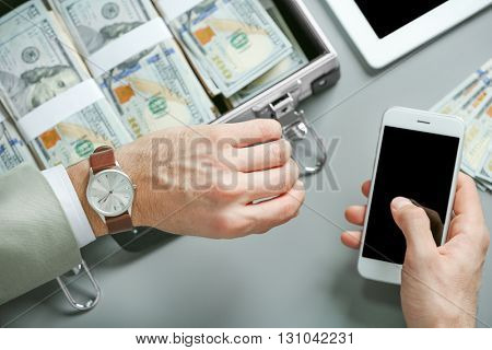 Businessman with case full of money, cellphone and watch, closeup