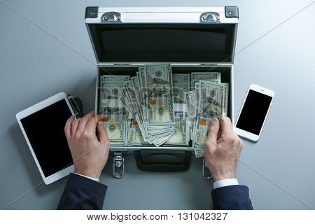Businessman with tablet counting money