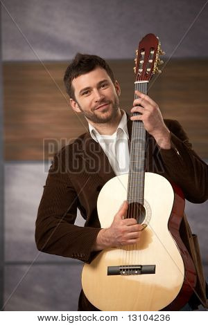 Handsome stylish guy standing holding guitar, smiling at camera.