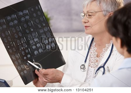 Doctor and patient discussing scan results in doctor's office.
