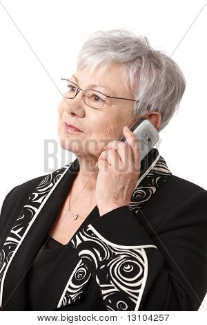 Closeup portrait of senior lady wearing glasses, using mobile phone, isolated on white.