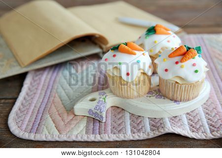 Cupcakes with frosting and decorative carrots on wooden stand