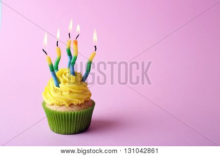 Birthday cupcake with candles on light pink background