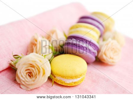 Fresh macaroons and roses on pink napkin, closeup