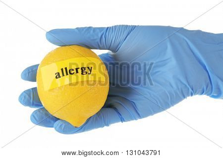 Allergic food concept. Hand in glove holding lemon isolated on white
