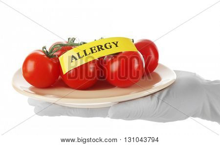 Allergic food concept. Hand in glove holding tomatoes isolated on white