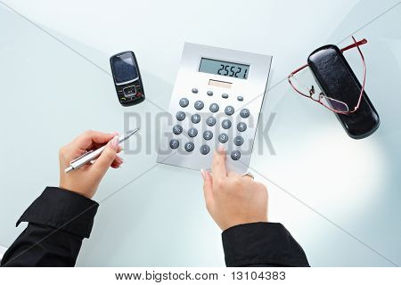 Female hands using digital calculator and holding pen.