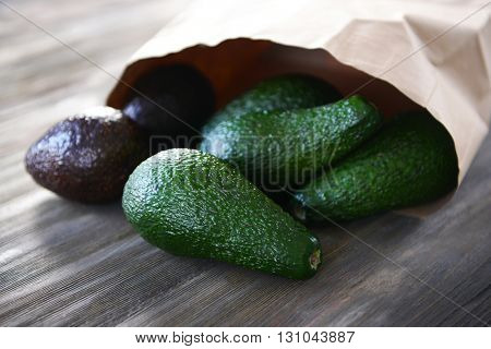 Fresh avocados in paper bag on wooden background