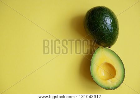 Fresh avocado on yellow background