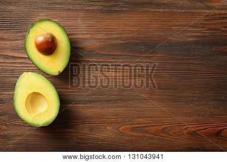 Avocado on wooden background, top view
