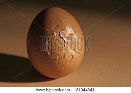 Cracked egg on dark beige background