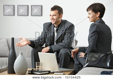 Young business people having meeting at office sitting on sofa talking to partner.