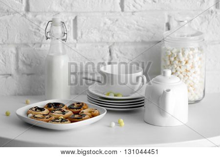 Cookies and tableware on white table