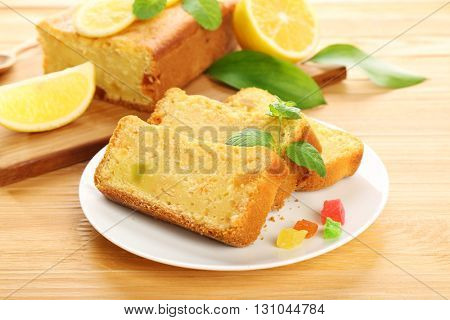 Pieces of delicious citrus cake on wooden table