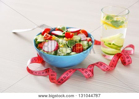 Fresh vegetarian salad and glass of lemonade on wooden table closeup