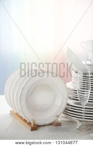 Set of new white dishes on wooden table, indoors
