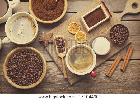 Cups of coffee with spices on wooden table, top view