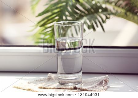 Glass of pure water on windowsill