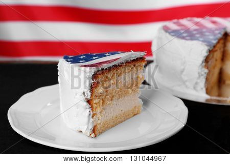 Piece of American flag cake, on black wooden background.