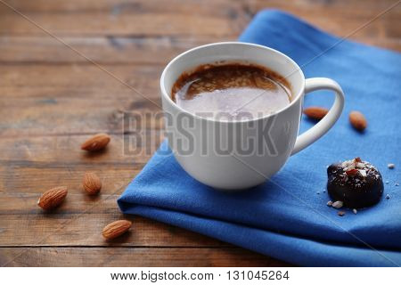 Cup of coffee with sweet on a blue napkin