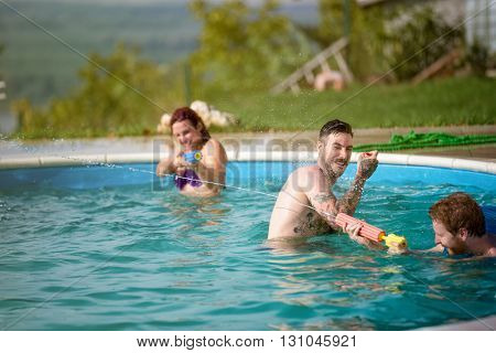 Guys and lassies having fun when spraying each other in open pool at summer