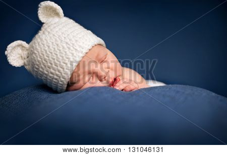 Three week old newborn baby boy wearing a brown crocheted bear hat and sleeping