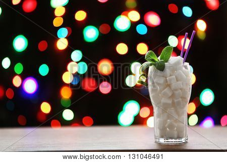 Glass with lump sugar on dark bokeh background
