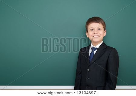 happy successfull school boy in black suit portrait on green chalkboard background, education concept