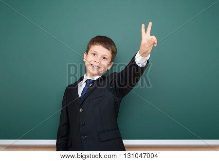 school boy in black suit portrait on green chalkboard background, education concept