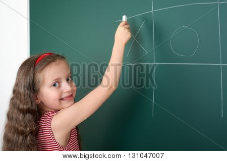 schoolgirl child in red striped dress drawing tic tac toe on green chalkboard background, summer school vacation concept
