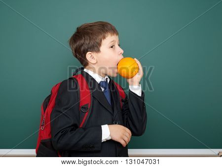 school boy eat orange in black suit on green chalkboard background with red backpack, education concept