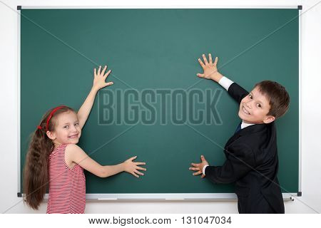 school boy and girl put hands on blank chalkboard and make frame, education concept