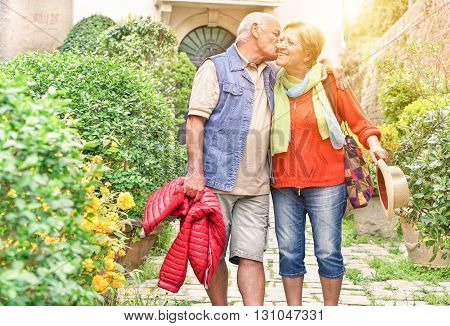 Happy playful senior couple in love tenderly enjoying romantic vacation for wedding anniversary celebration - Joyful elderly active lifestyle - Warm filter with artificial sunlight
