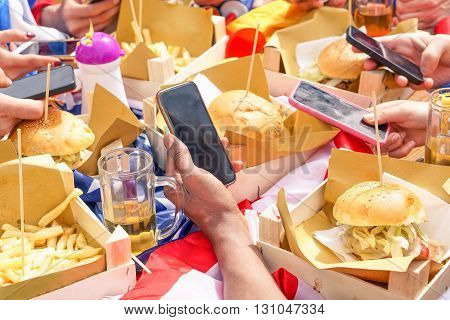 Group of friends having fun together with smartphones - Closeup of hands social networking with mobile cellphones beer and burgers - Technology addiction concept - Main focus on middle bottom hand